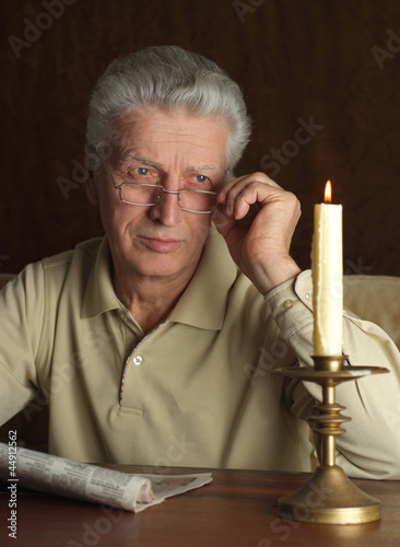 Beautiful Caucasian elderly man sitting at a table