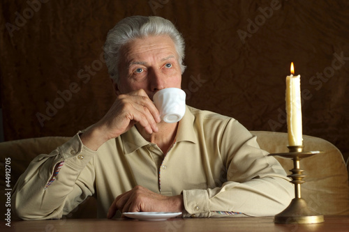 Beautiful Caucasian senior man sitting at a table