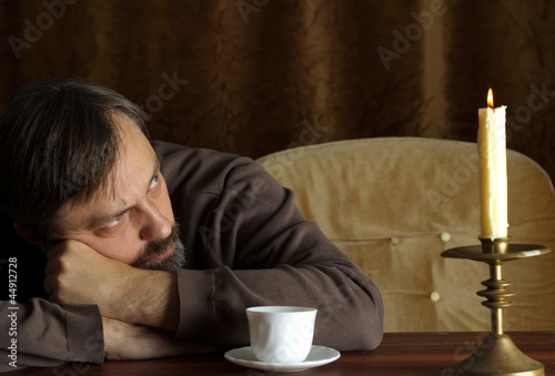 Beautiful Caucasian elderly male sitting at a table