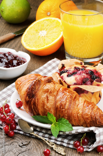 Breakfast with orange juice, fresh croissant and cake