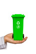Hand offer green trash can