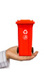Hand offer red trash can