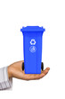 Hand offer blue trash can
