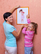 Woman and her daughter hanging up photo (of same girl)