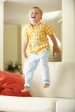 Young Boy Jumping On Sofa At Home