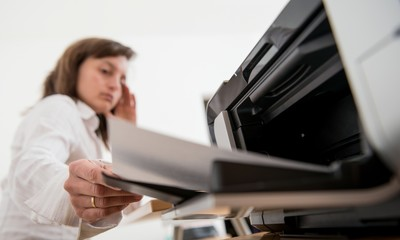 Depressed business person working with printer