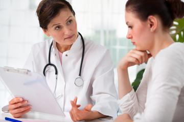 Ärztin berät eine junge Patientin