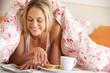 Pretty Woman Snuggled Under Duvet Eating Breakfast And Reading N