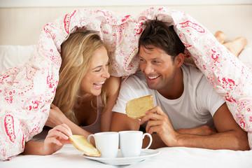 Couple Snuggled Under Duvet Eating Breakfast