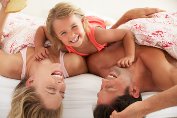 Family Relaxing Together In Bed