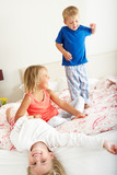 Children Bouncing On Bed