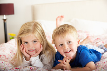 Two Children Relaxing On Bed