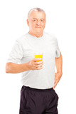 Mature athlete holding a glass of orange juice, refreshing after