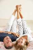 Senior Couple Lying Upside Down Together In Bed
