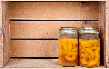 Canned peaches in a rustic crate