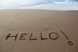 Brown sand beach with written word Hello