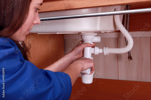 Woman fixing the plumbing on a sink