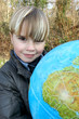 Little boy holding globe outdoors