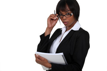 businesswoman with glasses lowered holding notebook