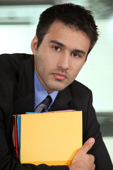 Eager young businessman falling behind with paper work