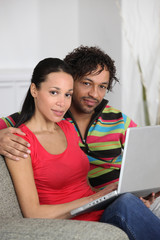 Couple at home using a laptop computer