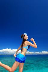 海辺でランニングを楽しむ女性