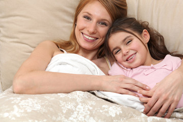 Mother and daughter in bed together