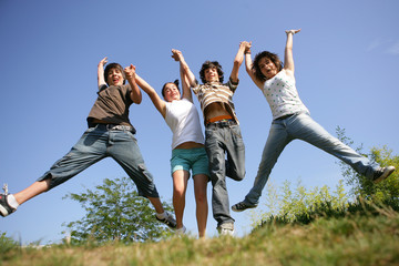 four teenagers jumping