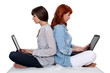 Two female friends sat back to back with laptops
