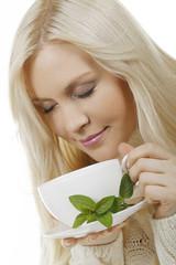 Hübsche Frau genießt eine Tasse Pfefferminztee