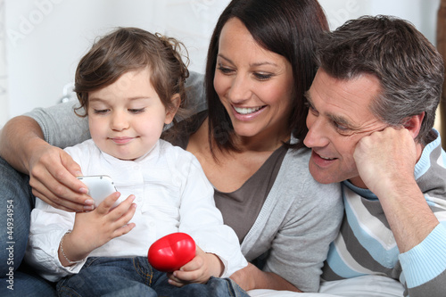 Toddler holding telephone whilst sat with parents on sofa