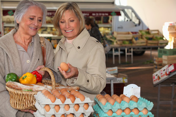 two senior women shopping on the market