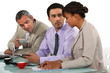Three business people having coffee during meeting