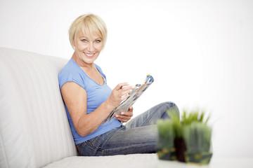 Frau liest eine Zeitschrift daheim