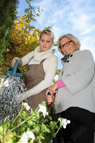 young woman helping a senior in the garden