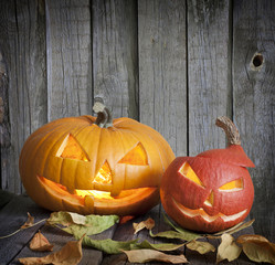 Halloween pumpkins on old grunge boards with leaves background