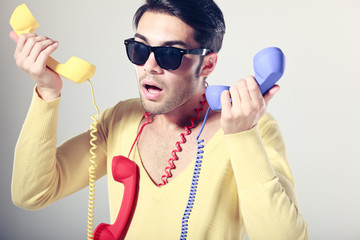 funny call center guy with hipster glasses and colouful phones