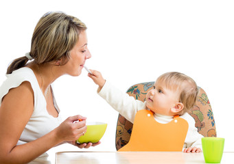 young mother spoon feeding her playful child girl isolated on wh