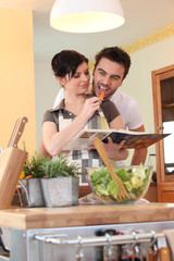 Young couple in a kitchen with a cookbook