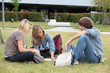 Three students studying on the grass