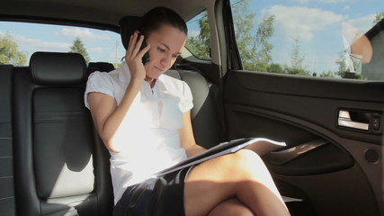 Busy businesswoman with documents and mobile phone in car