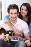 Couple sat on the couch with electric guitar