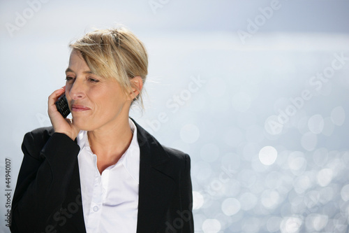 Blond businesswoman taking call by the ocean