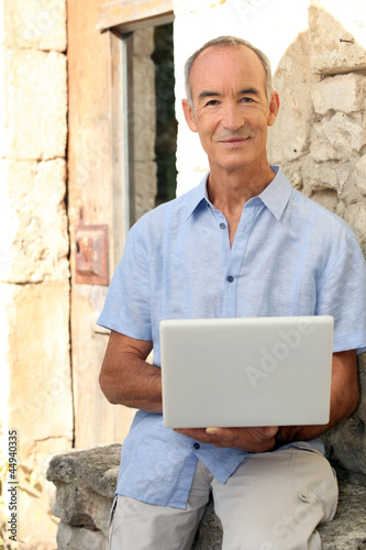 Grey haired man sat on stone wall with laptop