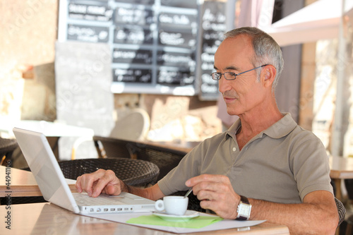 Senior man drinking coffee and checking his e-mails