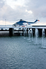 Big blue helicopter on a platform behind fountains in winter
