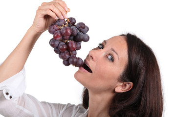 Brunette woman eating grapes