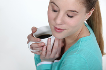 Woman warming herself with mug of coffee