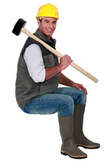 craftsman carrying huge hammer on his shoulder