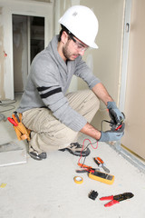 Man snipping wall wiring